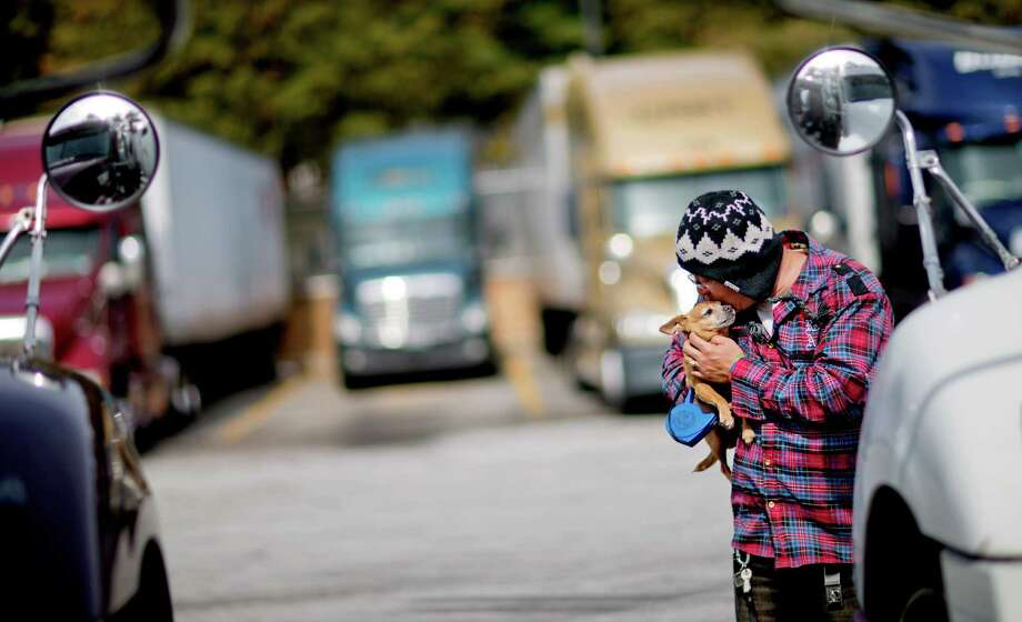 Truck driver Jimmy Mayes holds his chihuahua, Coco, while waiting to pick up a load at a truck stop Tuesday, Oct. 30, 2012, in Atlanta. Even amid a struggling economy with high unemployment, trucking companies had a tough time hiring young drivers willing to hit the road for long hauls. Now the U.S. is speeding toward a critical shortage of truck drivers in the next few years as the economy recovers and demand for goods increases, an expert in the inner-workings of supply chains said in a report Tuesday. (AP Photo/David Goldman) Photo: David Goldman, STF / AP