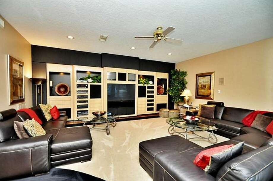 The family room has plush carpeting and built-in shelves that includes room for a large television. Photo: Picasa, RE/MAX Of Texas