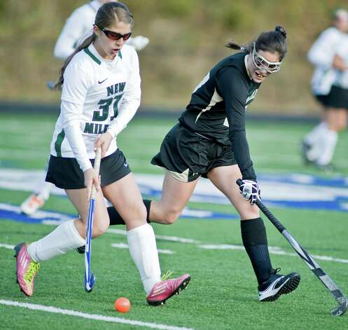 New Milford High School's Meghan Lacey moves the ball as Joel Barlow High School's Marissa Johnson tries to stop it in an SWC field hockey semifinal game at Immaculate. Sunday, Nov. 4, 2012 Photo: Scott Mullin / The News-Times Freelance