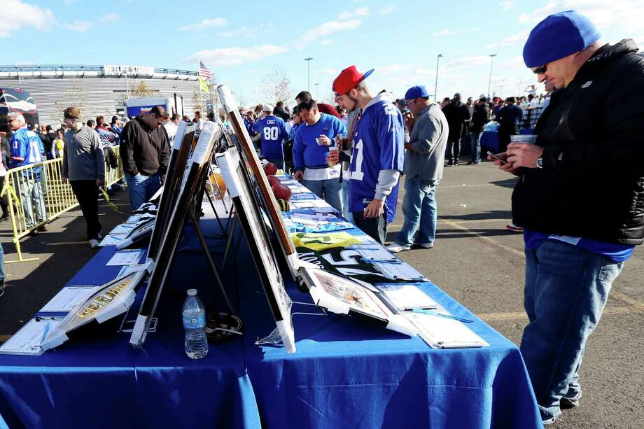 Fans look at items in a silent auction being held to raise money for people suffering from the affects of Superstorm Sandy and cystic fibrosis before an NFL football game between the New York Giants and the Pittsburgh Steelers, Sunday, Nov. 4, 2012, in East Rutherford, N.J. Photo: Julio Cortez