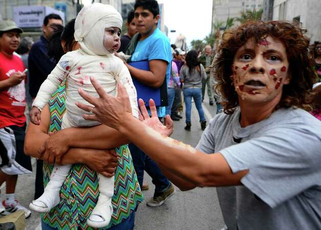 "A woman and a baby dressed up as zombies take part in a ""Zombie Walk"" at the Revolution Monument in Mexico City on November 3, 2012. According to organizers, 15,000 people will take part in the event in an attempt to set a new Guinness record.  AFP PHOTO/Alfredo EstrellaALFREDO ESTRELLA/AFP/Getty Images Photo: ALFREDO ESTRELLA, AFP/Getty Images / ALFREDO ESTRELLA"