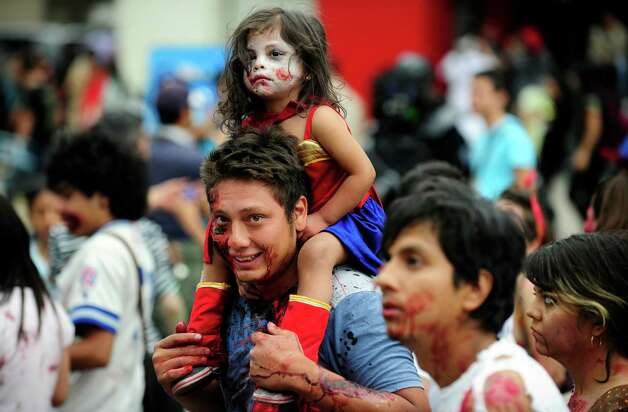 "A man and a girl dressed up as zombies take part in a ""Zombie Walk"" at the Revolution Monument in Mexico City on November 3, 2012. According to organizers, 15,000 people will take part in the event in an attempt to set a new Guinness record.  AFP PHOTO/Alfredo EstrellaALFREDO ESTRELLA/AFP/Getty Images Photo: ALFREDO ESTRELLA, AFP/Getty Images / AFP"