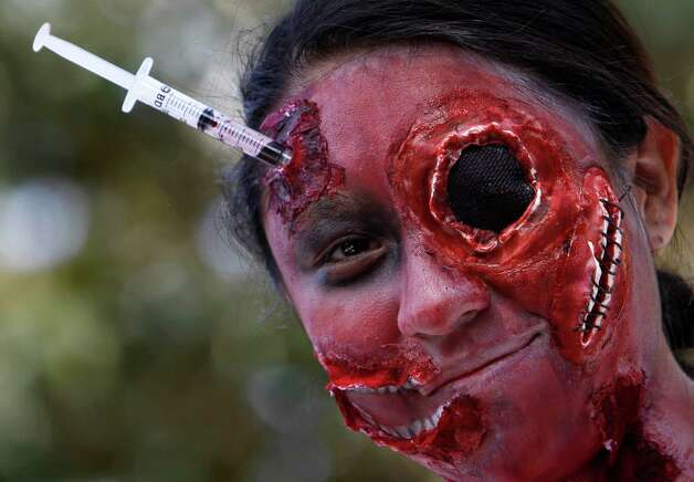 A woman wearing zombie make-up looks at the camera during the Zombie Walk in Mexico City, Saturday, Nov. 3, 2012. According to the organization Zombie Walk Mexico, they are trying to set a new Guinness World Record of the biggest Zombie Walk. (AP Photo/Marco Ugarte) Photo: Marco Ugarte, Associated Press / AP