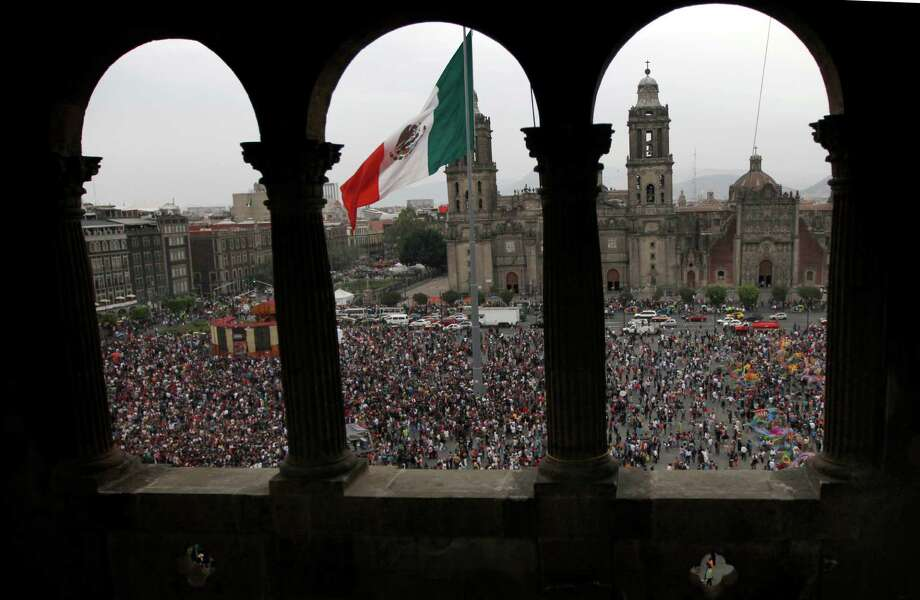 The Mexican flag flies in the main Zocalo plaza where people attend the Zombie Walk, seen from a city government building in Mexico City, Saturday, Nov. 3, 2012. At top is Metropolitan Cathedral. (AP Photo/Marco Ugarte) Photo: Marco Ugarte, Associated Press / AP