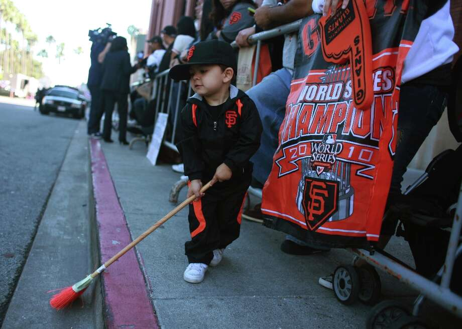 Miguel Diaz, 2, of Fairfield sweeps the street with his broom as he waits with his mother and father for the San Francisco Giants to arrive at AT&T Park after returning from Detroit where the Giants won the World Series in a four game sweep on Monday, October 29, 2012 in San Francisco, Calif. Photo: Lea Suzuki, The Chronicle / ONLINE_YES