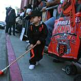 Miguel Diaz, 2, of Fairfield sweeps the street with his broom as he waits with his mother and father for the San Francisco Giants to arrive at AT&T Park after returning from Detroit where the Giants won the World Series in a four game sweep on Monday, October 29, 2012 in San Francisco, Calif.