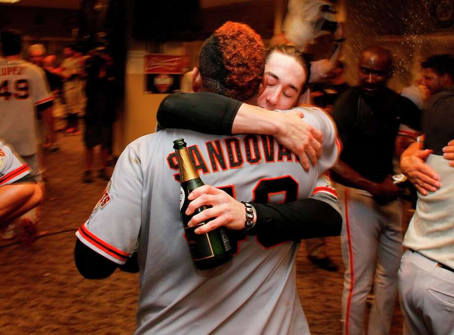 Giants' Pablo Sandoval and Tim Lincecum embrace, while the team celebrates in the clubhouse, as the San Francisco Giants beat the Cincinnati Reds 6-4 in game five to win the National League Division Series in Cincinnati, Ohio on Thursday Oct. 11, 2012. Photo: Michael Macor, The Chronicle / ONLINE_YES