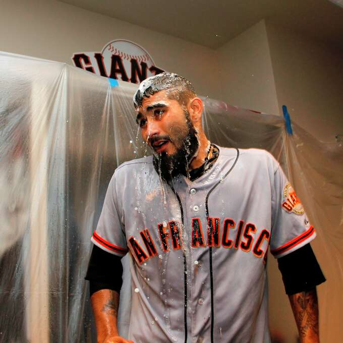 Giants' Sergio Romo gets a spray of champagne while the team celebrates in the clubhouse, as the San Francisco Giants beat the Cincinnati Reds 6-4 in game five to win the National League Division Series in Cincinnati, Ohio on Thursday Oct. 11, 2012. Photo: Michael Macor, The Chronicle / ONLINE_YES