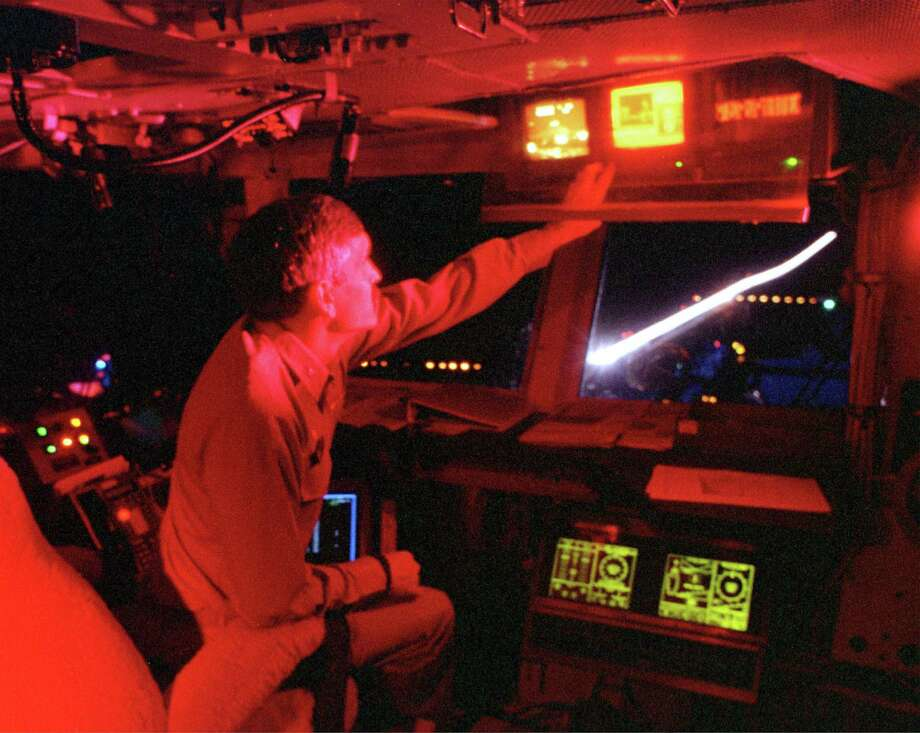 The light streak of the afterburner from an F/A-18 Hornet lights up the flight deck on the USS Enterprise as the commanding officer, Capt. Marty Chanik, monitors the first wave of strike aircraft launching from the deck into Iraq on December 17, 1998. Photo: U.S. Navy, Getty Images / Getty Images North America