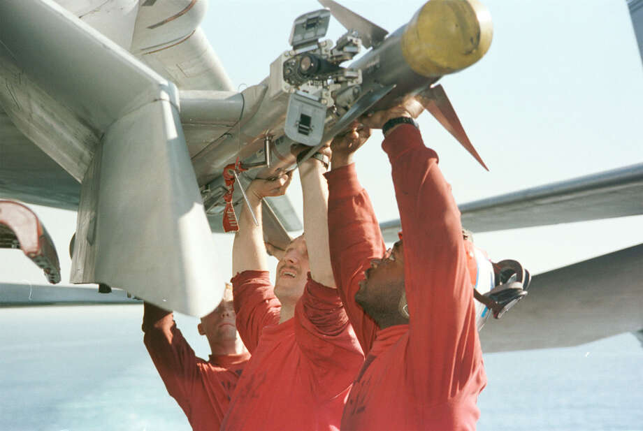 Aviation ordnancemen on the flight deck of the USS Enterprise load an F-14 Tomcat with an AIM-9 sidewinder missile in preparation for a second wave of attacks against Iraq in support of Operation Desert Fox December 17, 1998. Photo: U.S. Navy, Getty Images / Getty Images North America