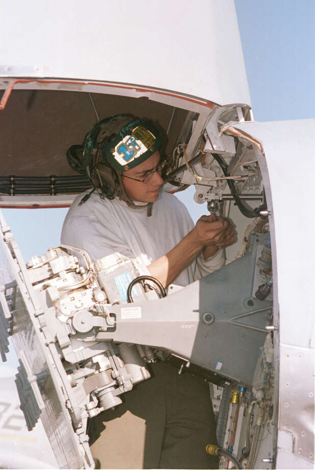 A crewman on board USS Enterprise conducts pre-flight maintenance on the radar of an F-14 Tomcat prior to a second wave of attacks against Iraq in support of Operation Desert Fox December 17, 1998. Photo: U.S. Navy, Getty Images / Getty Images North America