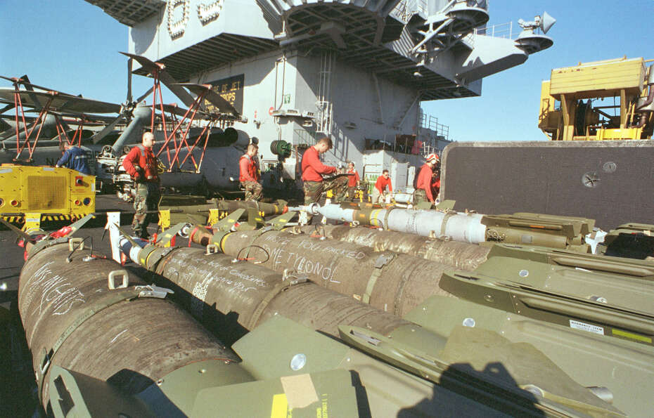 Bombs sit ready to be loaded onto various aircraft by crewmen of the USS Enterprise for a third wave