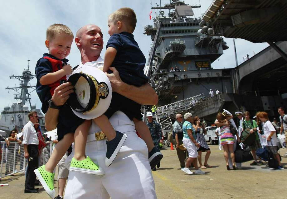 Lt. Brian Dennison hugs his twin boys, Logan and Grant, during the homecoming of the USS Enterprise at the Norfolk Naval Station July 15, 2011 in Norfolk, Va. Photo: Win McNamee, Getty Images / 2011 Getty Images