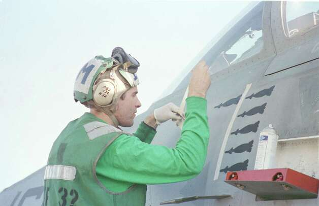 A crewman of the USS Enterprise takes advantage of a lull in activities, in between air strikes against Iraq, to paint icons of bombs on a squadron aircraft to symbolize the number of bombing runs. Photo: U.S. Navy, Getty Images / Getty Images North America