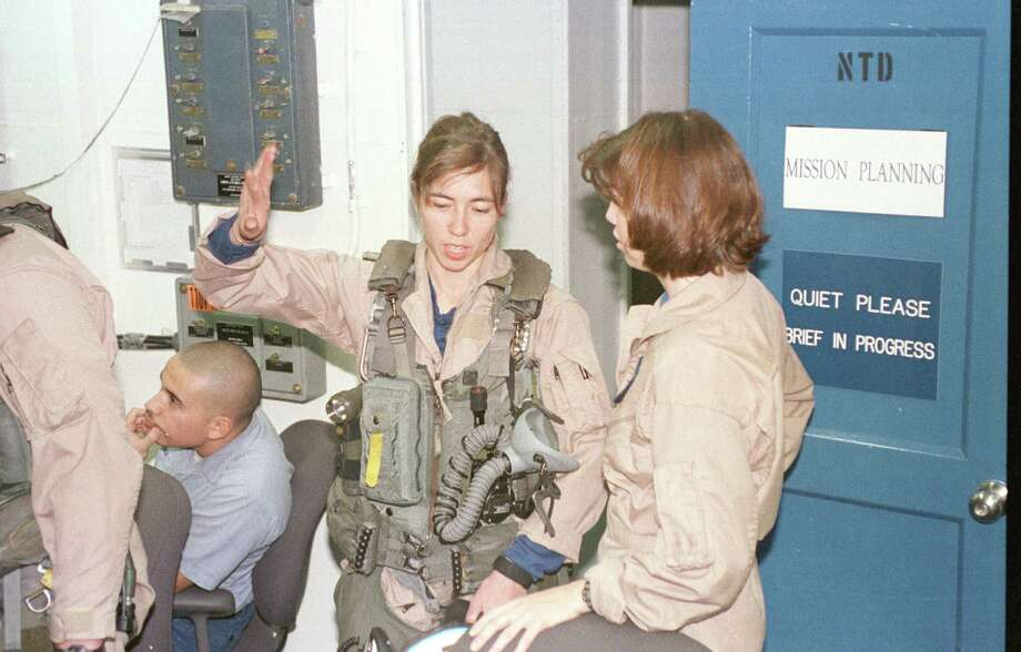 Lt. Carol Watts from Strike-Fighter Squadron 37 discusses her mission into Iraq with Lt. Lyndsi Bates aboard the USS Enterprise on December 15, 1998. Photo: U.S. Navy, Getty Images / Getty Images North America