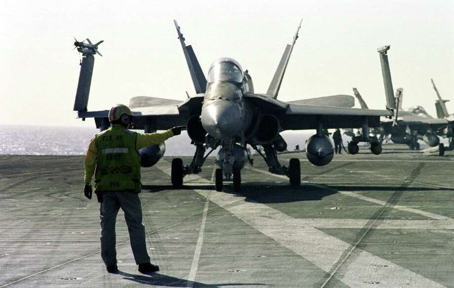 An aircraft director signals a pilot to turn his F/A-18C Hornet strike fighter while taxiing across the flight deck of the USS Enterprise on March 9, 1999, in the Mediterranean Sea. Photo: U.S. Navy, Getty Images / Getty Images North America