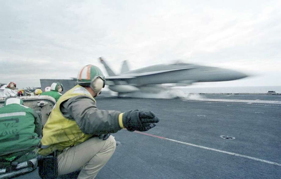 "The ""shooter"" gives the pilot of an F/A-18 Hornet the signal as his aircraft is launched from a catapult during flight operations on board USS Enterprise February 22, 1999. Photo: U.S. Navy, Getty Images / Getty Images North America"
