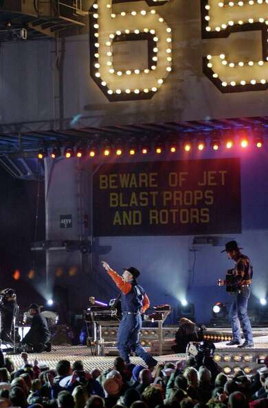Country singer Garth Brooks and his band perform on the flight deck of the USS Enterprise while dock