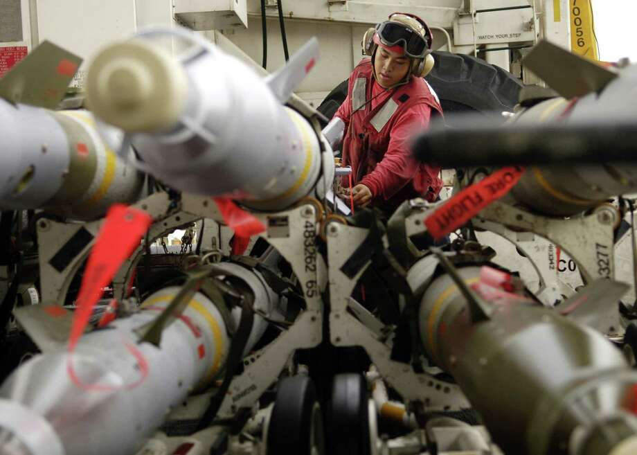 Ordnanceman Airman Wong Thao cleans and inspects ordnance staged in the bomb farm on the flight deck aboard the USS Enterprise on September 8, 2006 in the Arabian Sea. Photo: U.S. Navy, Getty Images / 2006 U.S. Navy