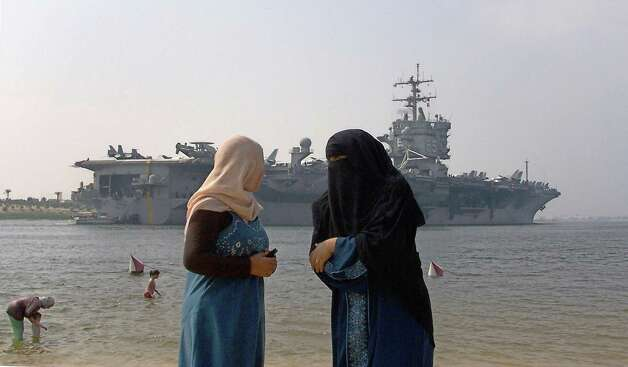 Two Egyptian women stand on a beach in the port city of Ismailia, on the Suez Canal, 120 kilometers north of Cairo, as the US nuclear-powered aircraft carrier USS Enterprise navigates towards the Gulf waters on August 1, 2007. Photo: STR, AFP/Getty Images / 2007 AFP