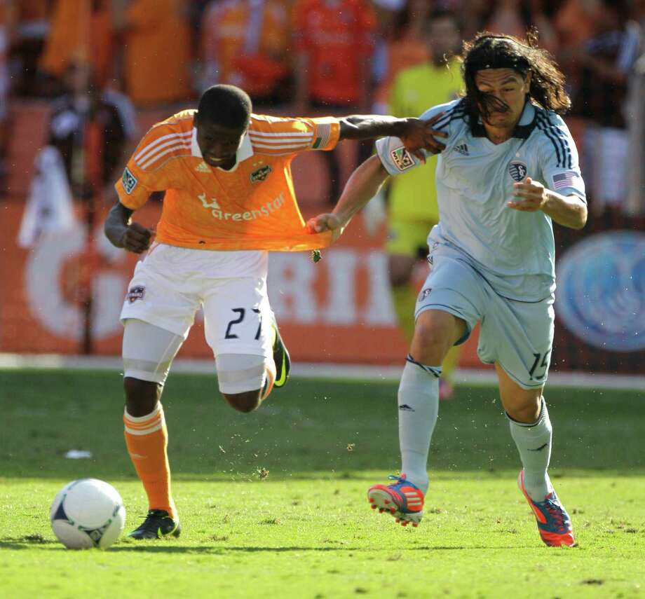 Houston Dynamo Boniek Garcia, left, and Sporting Kansas City Roger Espinoza battle for the ball during first half of the MLS Eastern Conference semifinal at the BBVA Compass Stadium Sunday, Nov. 4, 2012, in Houston. Photo: Melissa Phillip, Houston Chronicle / © 2012 Houston Chronicle