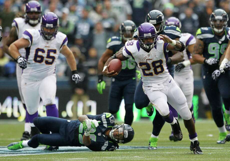 Minnesota Vikings' Adrian Peterson (28) leaves Seattle Seahawks' Earl Thomas, lower left, on the ground after breaking a tackle in the first half of an NFL football game, Sunday, Nov. 4, 2012, in Seattle. Photo: AP