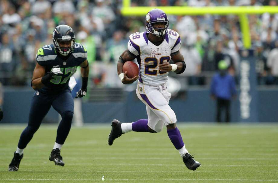 Minnesota Vikings' Adrian Peterson rushes with the ball as Seattle Seahawks' Mike Morgan pursues in the first half of an NFL football game, Sunday, Nov. 4, 2012, in Seattle. Photo: AP