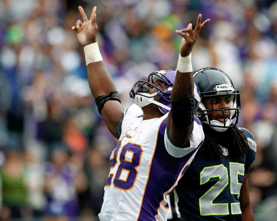 Minnesota Vikings' Adrian Peterson reacts to scoring his second touchdown of the game as Seattle Seahawks' Richard Sherman stands at right, in the first half of an NFL football game, Sunday, Nov. 4, 2012, in Seattle. Photo: AP
