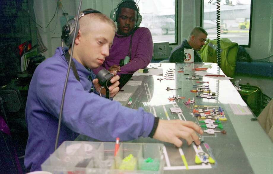 "Airman Jeffrey Hedgespeth controls the templates on a ""Ouija"" board used to keep track of the aircraft on the flight deck aboard the USS Enterprise on November 9, 1998, during a deployment to the Persian Gulf in support of Operation Southern Watch. Photo: U.S. Navy, Getty Images / Getty Images North America"