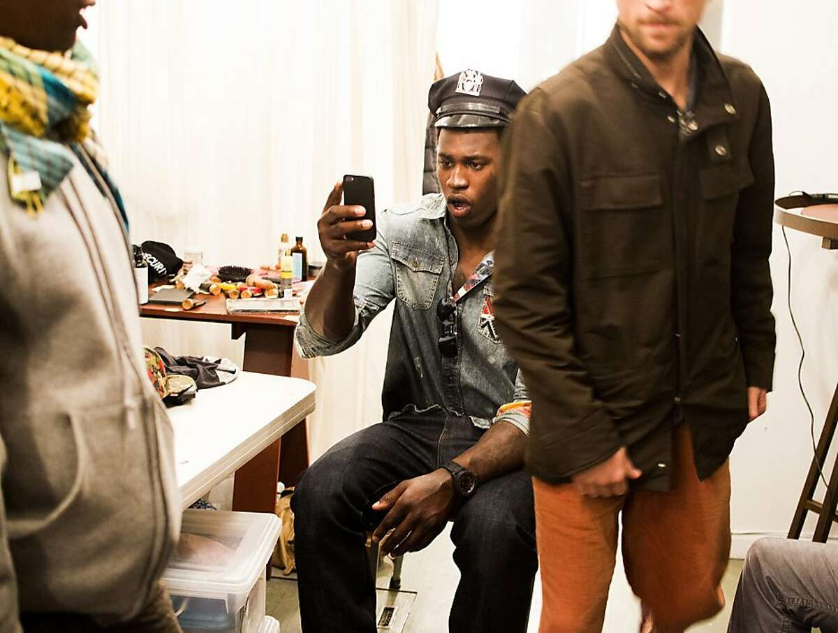 49ers linebacker Aldon Smith takes a picture of himself wearing a policeman's hat while on the set of
