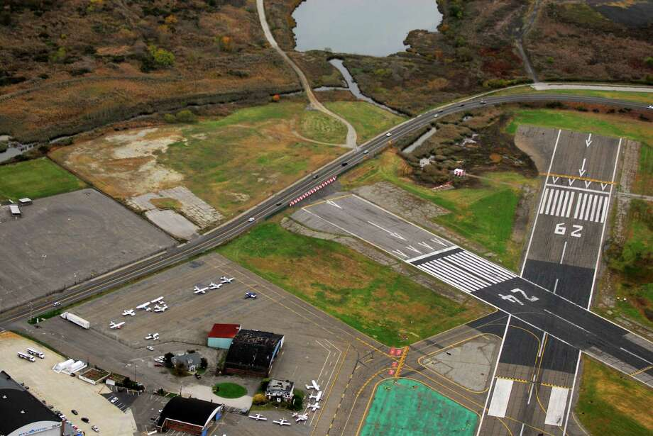 Morgan Kaolian/AEROPIX Main Street in Straford, Conn. winds past the blast fence at the end of Runway 6-24 at Sikorsky Memorial Airport. The recent aggreement will allow a runway safety zone and straighten out the dangerous curves with a relocation of Main St. and ease potential flooding. Photo: Morgan Kaolian, Morgan Kaolian/AEROPIX / Connecticut Post Freelance