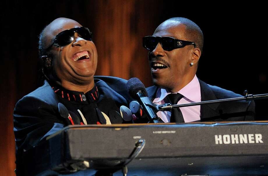 "Stevie Wonder, left, is joined by Eddie Murphy to sing Wonder's song ""Higher Ground"" onstage during ""Eddie Murphy: One Night Only,"" a celebration of Murphy's career at the Saban Theater on Saturday, Nov. 3, 2012, in Beverly Hills, Calif. (Photo by Chris Pizzello/Invision) Photo: Chris Pizzello"