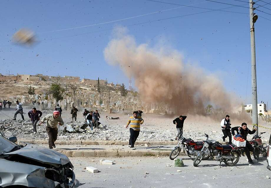 On the same day as the fighting in eastern Syria, civilians race for safety as a bomb explodes at a site where they were attempting a rescue in the northern Syrian city of Al-Bab. Photo: Philippe Desmazes, AFP/Getty Images