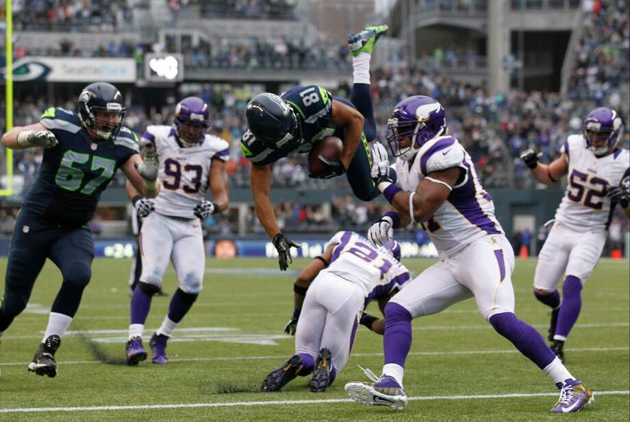 Seattle Seahawks' Golden Tate (81) leaps over Minnesota Vikings' Josh Robinson as Vikings' Everson Griffen, second from right, moves in as Tate runs for a touchdown in the first half of an NFL football game, Sunday, Nov. 4, 2012, in Seattle. Photo: AP