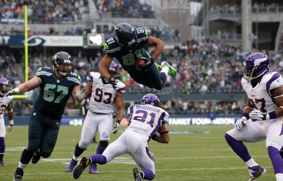 Seattle Seahawks' Golden Tate (81) leaps over Minnesota Vikings' Josh Robinson as he runs for a touchdown in the first half of an NFL football game, Sunday, Nov. 4, 2012, in Seattle. Photo: AP