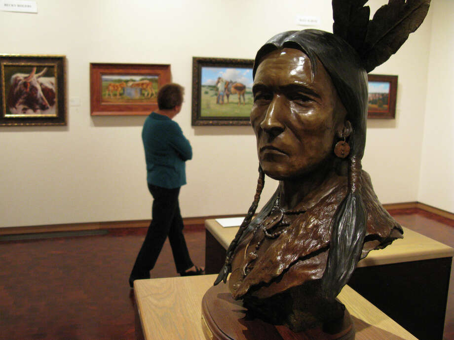 """The Skeptic"" a bronze bust by Tom Moss keeps watch as paintings on exhibit at The Museum of Western Art in Kerrville are examined by Marilyn Andrus, a museum volunteer (rear). Zeke MacCormack/Express-News"