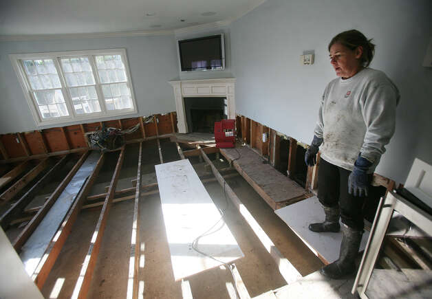 Sue Slobin looks at the state of her living room in the aftermath of Hurricane Sandy at 24 Fairfield Beach Road in Fairfield on Sunday, November 4, 2012. Slobin, who had nine inches of water in her house, had to partially gut the first floor, including flooring and baseboard heating. Photo: Brian A. Pounds / Connecticut Post