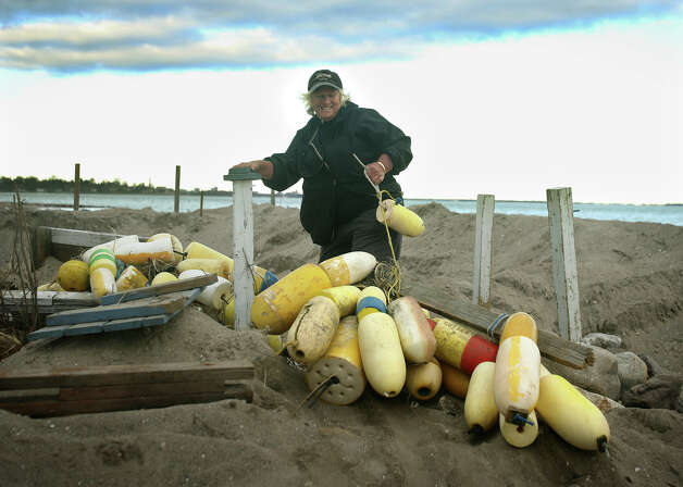 Paige Herman, president of the Fairfield Beach Association, pulls her buoy collection back to her waterfront home in the aftermath of Hurricane Sandy in Fairfield on Sunday, November 4, 2012. Photo: Brian A. Pounds / Connecticut Post