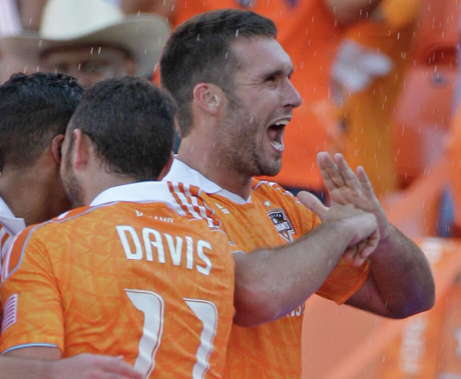 Houston Dynamo Will Bruin, right, celebrates his goal with teammate Brad Davis, left, and others during second half against the Sporting Kansas City during the MLS Eastern Conference semifinal at the BBVA Compass Stadium Sunday, Nov. 4, 2012, in Houston. Photo: Melissa Phillip, Houston Chronicle / © 2012 Houston Chronicle