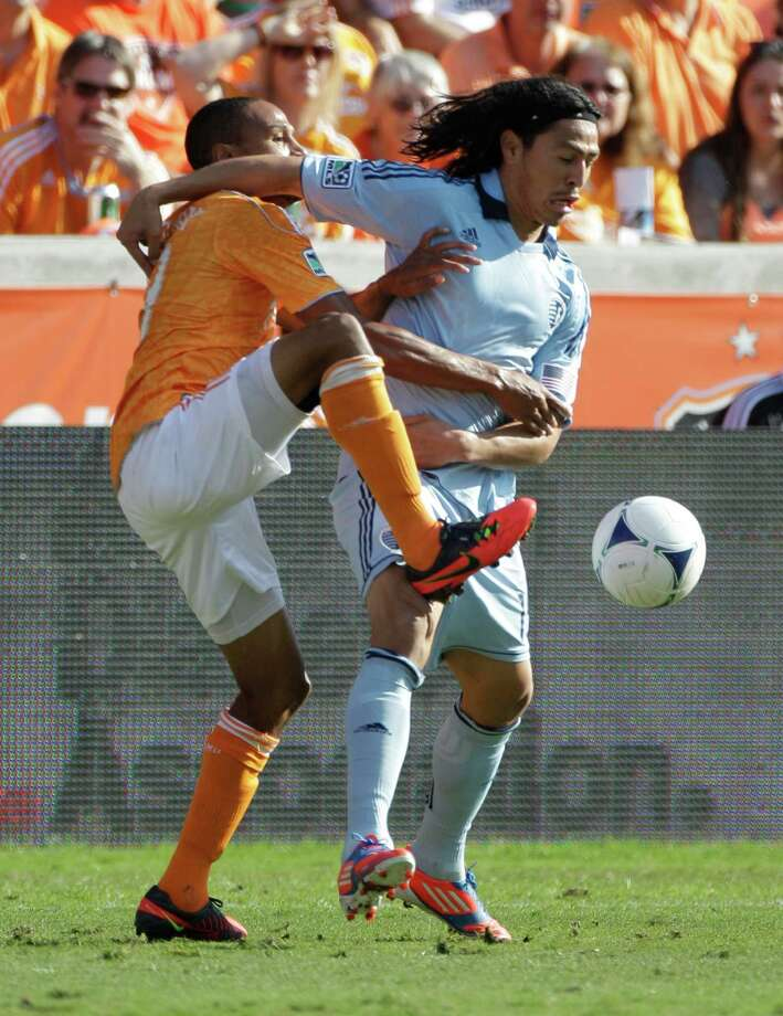 Houston Dynamo Ricardo Clark, left, and Sporting Kansas City Roger Espinoza, right, tangle for control of ball during the MLS Eastern Conference semifinal at the BBVA Compass Stadium Sunday, Nov. 4, 2012, in Houston. Photo: Melissa Phillip, Houston Chronicle / © 2012 Houston Chronicle