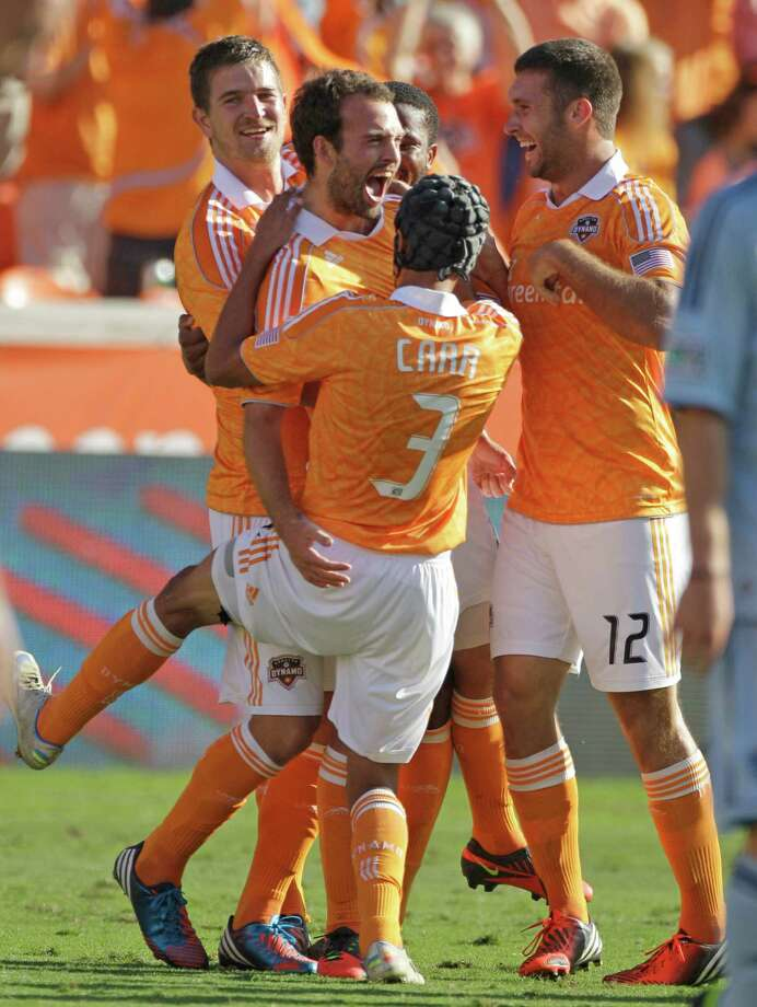 Houston Dynamo Adam Moffat, left center, celebrates his goal with teammate (3) Calen Carr and Will bruin, right, and others during first half against the the Sporting Kansas City in the MLS Eastern Conference semifinal at the BBVA Compass Stadium Sunday, Nov. 4, 2012, in Houston. Photo: Melissa Phillip, Houston Chronicle / © 2012 Houston Chronicle