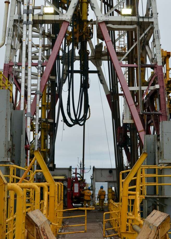 Onboard the Noble Discoverer, workers on the rig floor link up drill pipe. Shell is using the ship and its crew to finish the first half of a well in its Burger prospect in the Chukchi Sea -- with a plan to return next year and drill it to completion. (Photo: Jennifer A. Dlouhy / The Houston Chronicle) (Houston Chronicle)