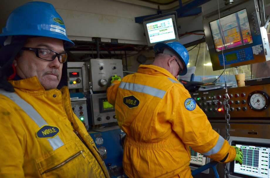 "Kendall Duncan, assistant rig manager, and driller Sheldon Smith coordinate operations inside the drill shack on the Noble Discoverer. Duncan, who is from Poplarville, Miss., says he is still adjusting to the Arctic climate -- including the patches of ice that appear on the vessel. ""It's like waking up in the Twilight Zone,"" Duncan says. (Photo: Jennifer A. Dlouhy / The Houston Chronicle) (Houston Chronicle)"