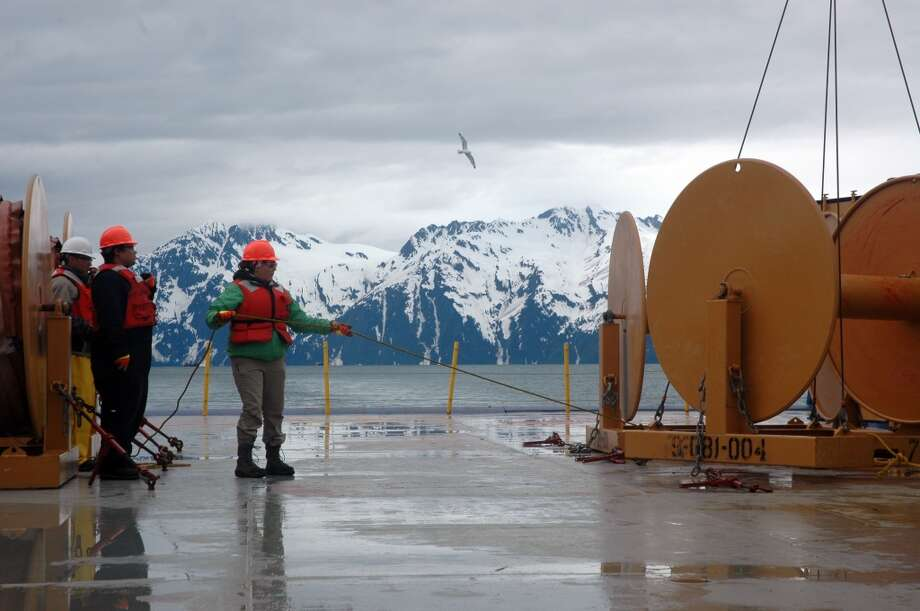 Priscilla Ridley holds a rope before equipment is hoisted on Shell's Nanuq oil recovery and supply vessel, during oil spill response training in Valdez, Alaska. The Chugagh Mountains are in the background. (Jennifer A. Dlouhy / The Houston Chronicle) (The Houston Chronicle)
