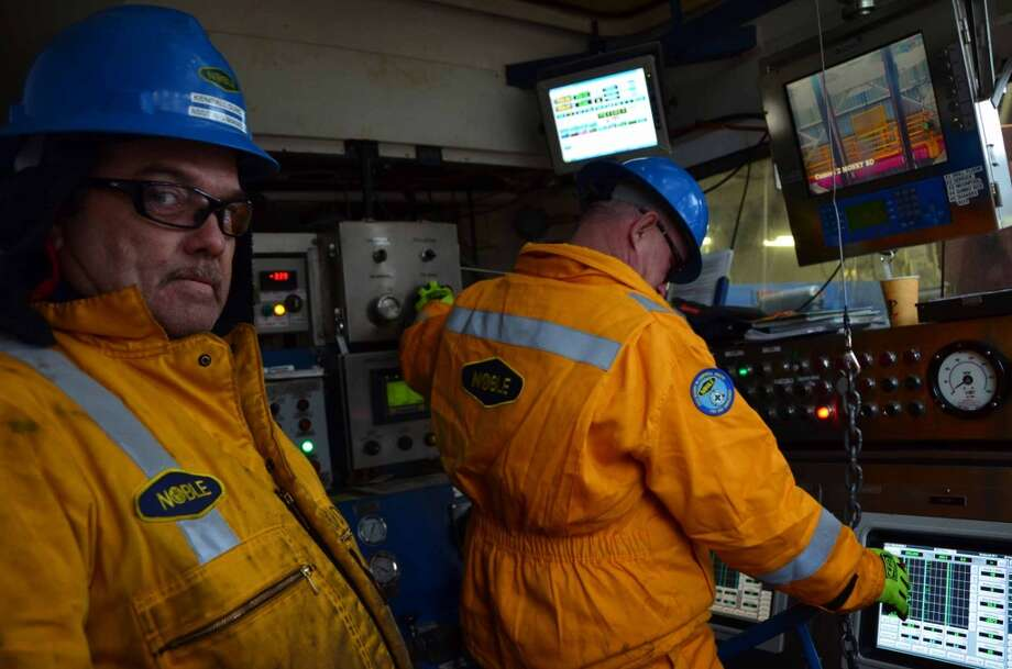 "Kendall Duncan, assistant rig manager, and driller Sheldon Smith coordinate operations inside the drill shack on the Noble Discoverer. Duncan, who is from Poplarville, Miss., says he is still adjusting to the Arctic climate -- including the patches of ice that appear on the vessel. ""It's like waking up in the Twilight Zone,"" Duncan says. (Photo: Jennifer A. Dlouhy / The Houston Chronicle) (Jennifer A. Dlouhy)"