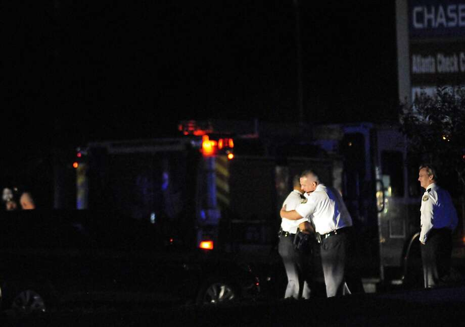 Law enforcement personnel embrace early Sunday, Nov. 4, 2012, as others investigate the scene of an Atlanta Police Department helicopter crash that killed two officers aboard the aircraft when it crashed near a shopping center late Saturday, Nov. 3, 2012. (AP Photo/David Tulis) Photo: David Tulis, Associated Press
