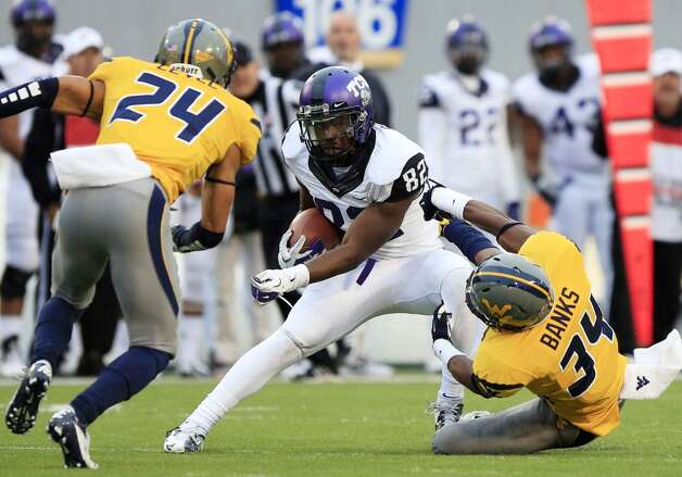 TCU wide receiver Josh Boyce (82) slips tackles by West Virginia's Cecil Level (24) and Ishmael Banks (34) during their NCAA college football game in Morgantown, W.Va., on Saturday, Nov. 3, 2012. TCU won 39-38 in overtime. (AP Photo/Christopher Jackson) (Associated Press)