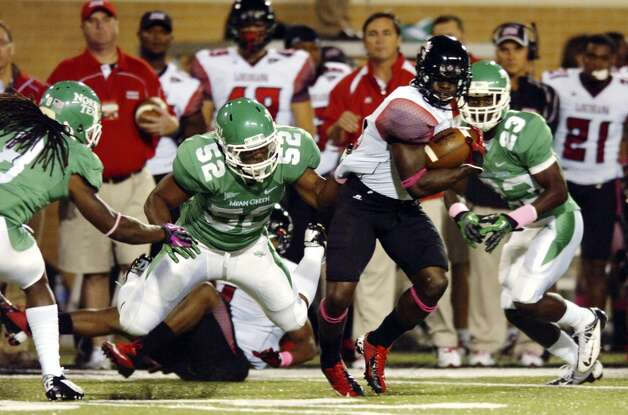 Louisiana-Lafayette wide receiver Harry Peoples, second from right, runs under pressure from North Texas linebacker Derek Akune (52) during their NCAA college football game, Tuesday, Oct. 16, 2012, in Denton, Texas. (AP Photo/The Denton Record-Chronicle, David Minton) (Associated Press)