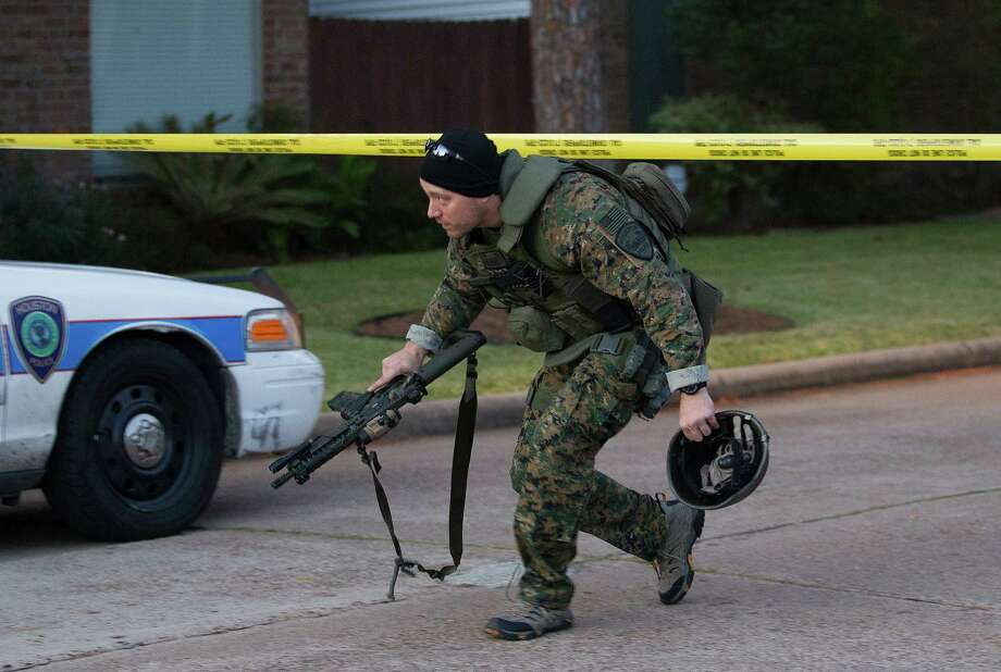 A Houston Police Department Swat Team member crosses the police line after a west Houston standoff on Sunday, Nov. 4, 2012, in Houston. The suspect was shot by officers and died at the scene. Photo: J. Patric Schneider, For The Chronicle / © 2012 Houston Chronicle
