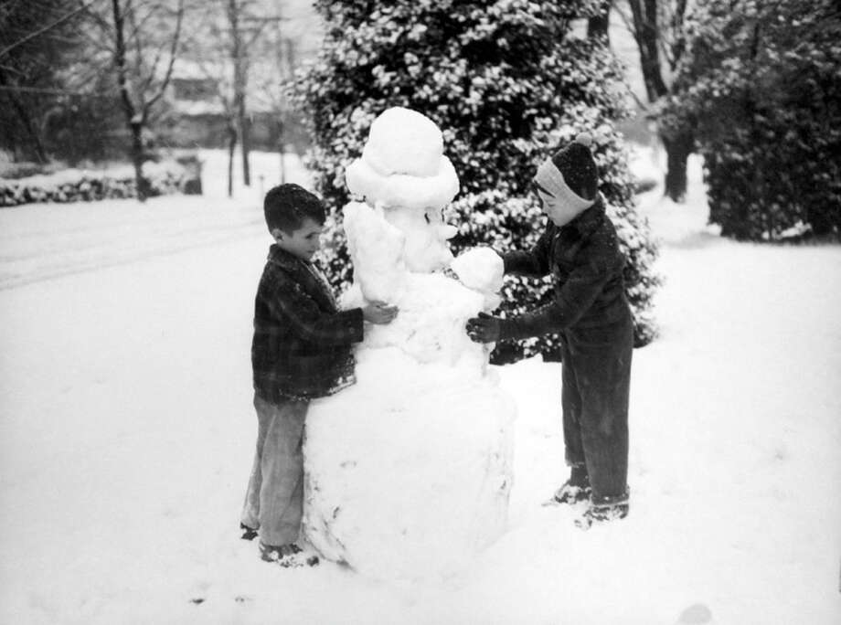 This picture from the snowstorm of Jan. 19, 1943 shows Howard Swalwell and Larry Sullins making a snowman. The negative was preserved at MOHAI, but P-I staff did not record who photographed the scene or where exactly it was taken. (Copyright MOHAI, Seattle Post-Intelligencer Collection, PI28396. Click for reproductions.) Photo: -